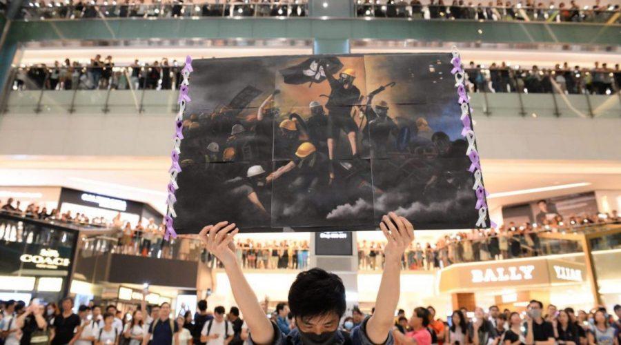 """Muž drží plakát v nákupním středisku v oblasti Sha Tin v Hongkongu 11. září 2019, aby zpíval nedávno napsanou protestní píseň s názvem """"Sláva Hongkongu"""", která si ve městě získala popularitu. (Huang Xiaoxiang / Epoch Times)"""