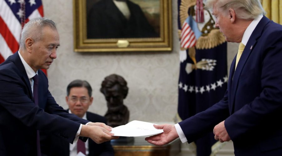 """Čínský vicepremiér Liou Che předává americkému prezidentovi Donaldu Trumpovi dopis čínského vůdce Si Ťin-pchinga poté, co Trump oznámil dosažení obchodní dohody """"fáze 1"""", 11. října 2019, USA. (Win McNamee / Getty Images)"""