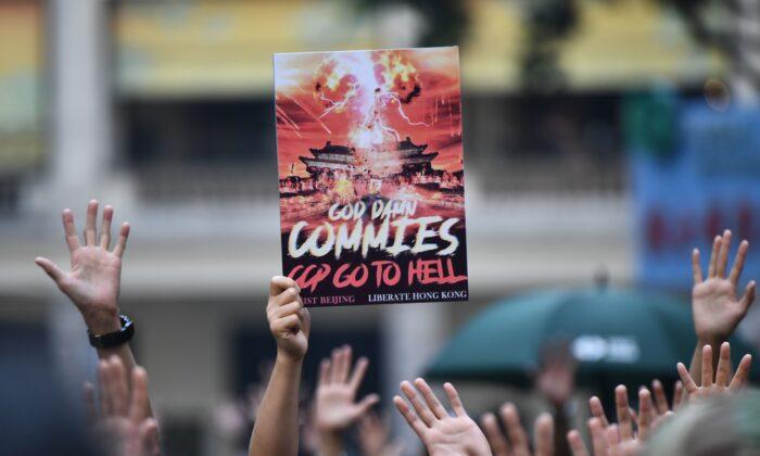 """Protestující v Hongkongu drží plakát s nápisem """"Bůh zatratil komunisty, Komunistická strana Číny půjde do pekla"""". Ostatní ukazují nad hlavou pět prstů symbolizujících pět požadavků, které chtějí, aby vláda podepsala. 1. října 2019, k 70. výročí založení čínského komunistického režimu. (ANTHONY WALLACE / AFP / Getty Images)"""