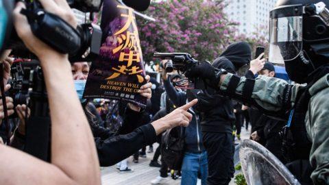 Žena čelí hlavni zbraně, zatímco drží plakát Epoch Times na protest proti hongkongské policii