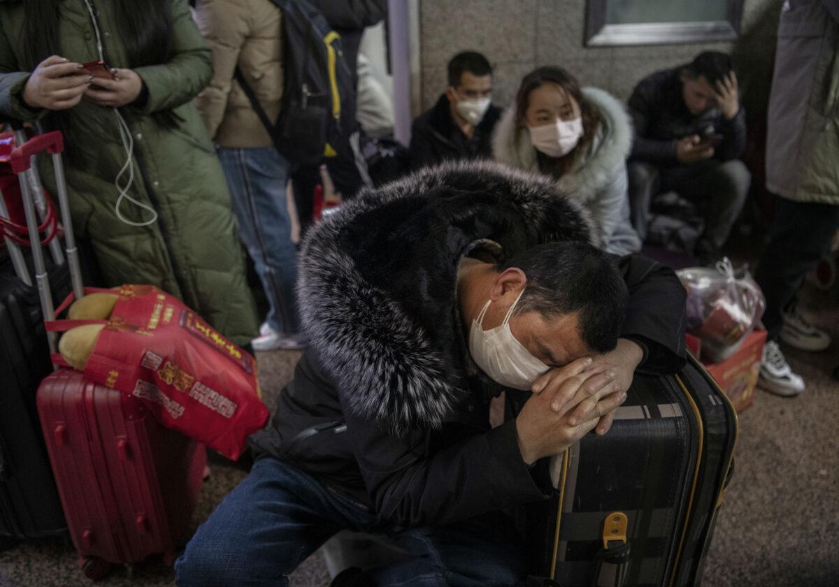 Číňan nosící ochrannou masku pospává na pekingském nádraží. Miliony lidí vyrazilo tento týden na cestu do svých domovů, aby srodinami oslavili největší svátky vroce – čínský nový rok. 23. ledna 2020. (Kevin Frayer / Getty Images)