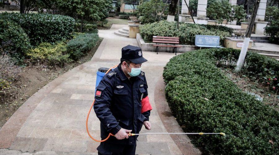 Bezpečnostní pracovník rozstřikuje alkohol za účelem dezinfekce, ve městě Wuhan, provincie Chu-pej, Čína 23. ledna 2020. (Getty Images)