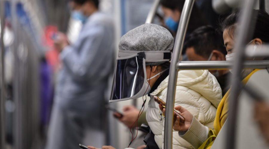Lidé v čínském metru sledují zprávy na chytrých telefonech, zatímco nosí ochranné masky a roušky, Šanghaj, Čína, 5. března 2020. (HKTOR RETAMAL / AFP prostřednictvím Getty Images)