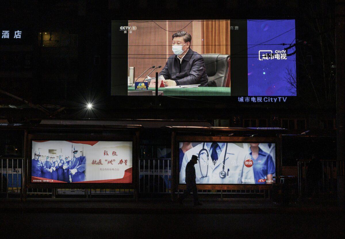 Velká obrazovka ukazuje čínského vůdce Si Ťin-pchinga v ochranné roušce během jeho návštěvy Wu-chanu, ve večerním zpravodajství čínské státní televize CCTV, 10. března 2020. (Kevin Frayer / Getty Images)