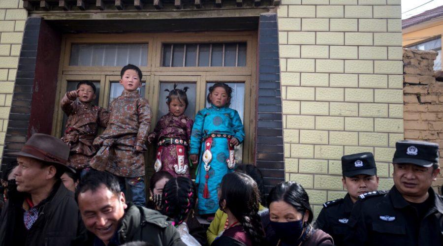 Děti v tradičním tibetském oděvu a policejní dohled nad procházejícími tibetskými buddhistickými mnichy během obřadu pro Monlam, jinak známého jako Velký modlitební festival v Losaru, tibetský Nový rok, v klášteře Rongwo, v kraji Tongren, v provincii Huangnan, Tibetská autonomní oblast, 1. března 2018. (Johannes Eisele / AFP prostřednictvím Getty Images)
