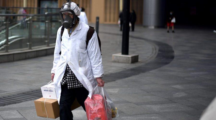 Muž v masce nese nákupní tašky při odchodu ze supermarketu v čínském městě Wu-chan v provincii Chu-pej, 30. března 2020. (NOEL CELIS / AFP prostřednictvím Getty Images)