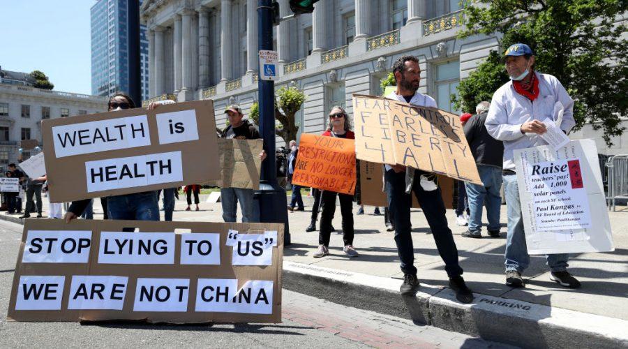 """Demonstranti protestují proti krokům Kalifornské vlády. Pokračují protesty proti celostátnímu nařízení k """"ukrývání se v domovech"""" před epidemií. Před obecní radnicí v San Franciscu v Kalifornii, 1. května 2020. (Justin Sullivan / Getty Images)"""