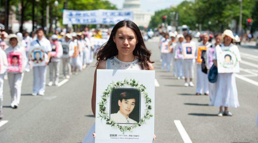 Žena drží fotografii muže zabitého při pronásledování Falun Gongu čínským režimem během protestní akce ve Washingtonu, USA, 17. července 2014. (Larry Dye/The Epoch Times)