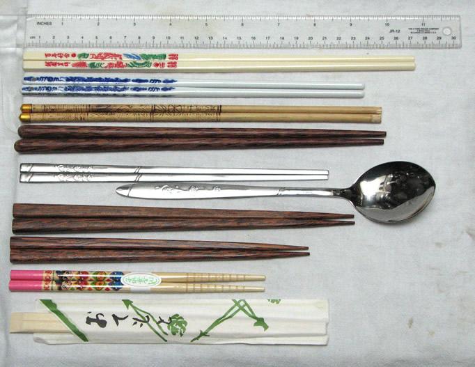 Různé typy jídelních hůlek. Seshora dolů: tchajwanské z melaminu, čínské porcelánové hůlky, tibetské bambusové hůlky, vietnamské z palmového dřeva, korejské hůlky z nerezové oceli v sadě se lžicí, japonské hůlky pro muže a ženu, japonské hůlky pro děti, jednorázové bambusové hůlky zabalené v papíru. (FiveRings/Wikimedia CC BY-SA 3.0)