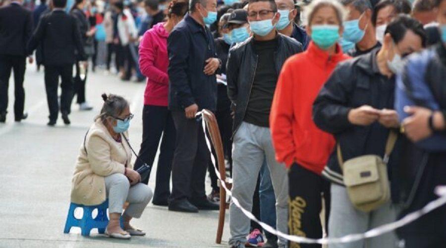 Obyvatelé čekají na testování COVID-19 v čínském městě Čching-tao ve východní čínské provincii Šan-tung, 12. října 2020. (STR / AFP prostřednictvím Getty Images)