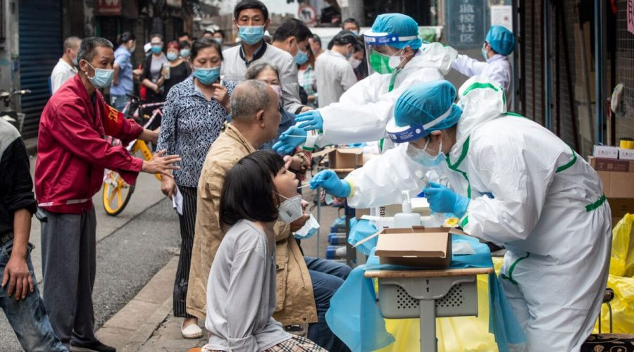 Zdravotničtí pracovníci odebírají obyvatelům vzorky prostřednictvím výtěrů, které mají být testovány na koronavirus COVID-19. Na ulici ve městě Wu-chan v čínské provincii Chu-pej, 15. května 2020. (STR / AFP prostřednictvím Getty Images)