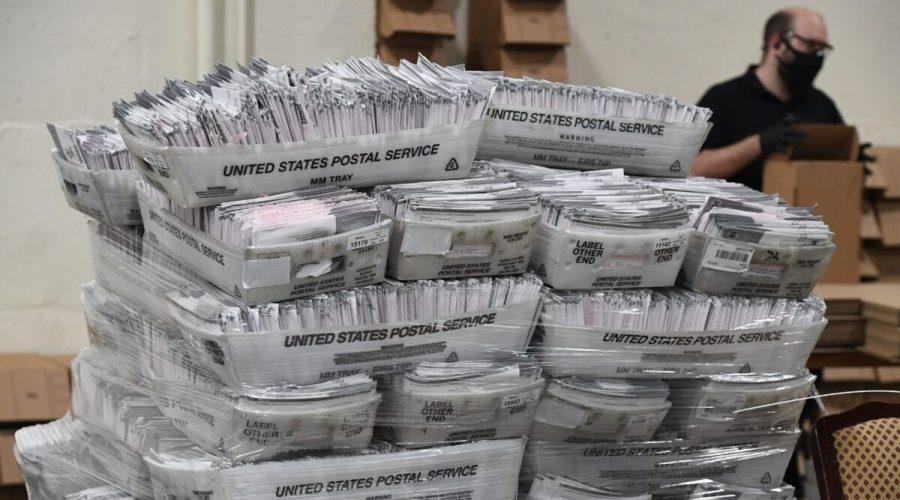 Poštovní hlasovací lístky čekají v obálkách na zpracování, USA, 28. října 2020. (ROBYN BECK / AFP prostřednictvím Getty Images)
