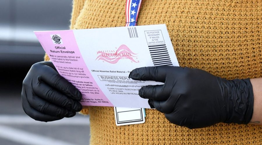 Pracovnice volebního oddělení okresu Clark přijímá hlasovací lístky na volebním oddělení 13. října 2020, Nevada. (Ethan Miller / Getty Images)