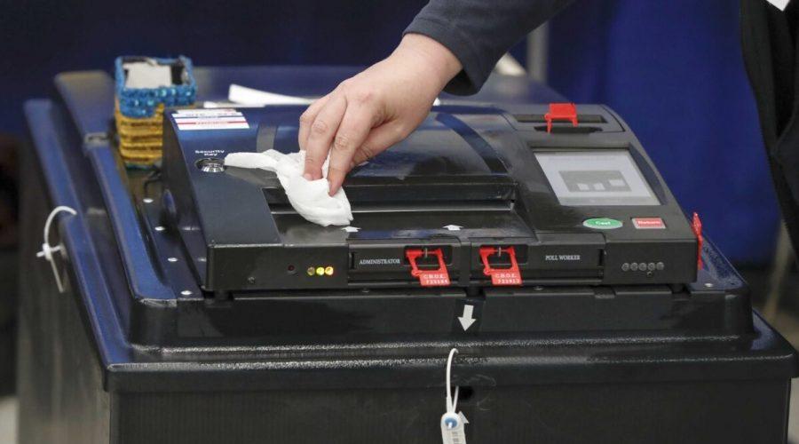 Zaměstnanec čistí hlasovací zařízení 17. března 2020, USA. (Kamil Krzaczynski / AFP přes Getty Images)