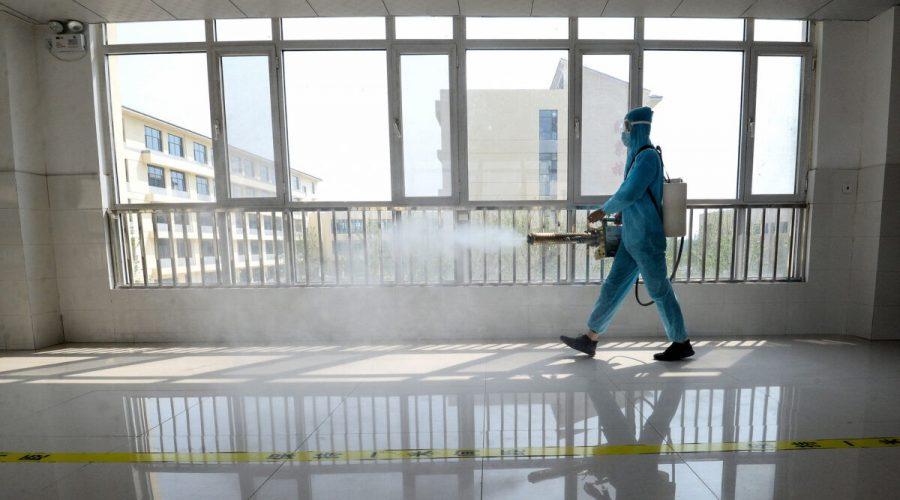 Zaměstnanec v ochranném obleku stříká dezinfekční prostředek ve městě Handan v provincii Che-pej v Číně, 30. srpna 2020. (STR / AFP prostřednictvím Getty Images)