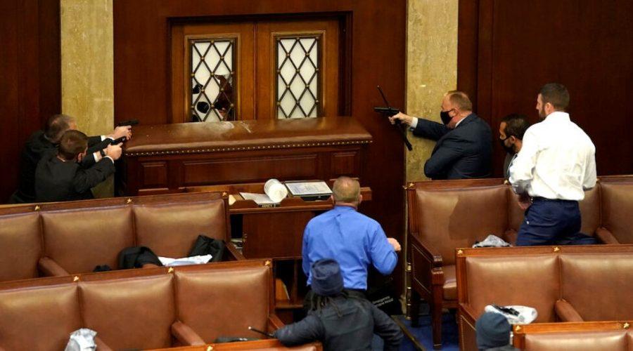 Stráž kapitolu míří zbraněmi na dveře, jejichž sklo bylo proraženo protestujícími, kteří vnikli do budovy Kapitolu během společného zasedání kongresu ve Washingtonu 6. ledna 2021. (Drew Angerer / Getty Images)