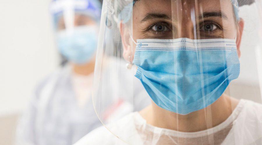Zdravotní sestra s ochrannou maskou a plastovým obličejovým štítem