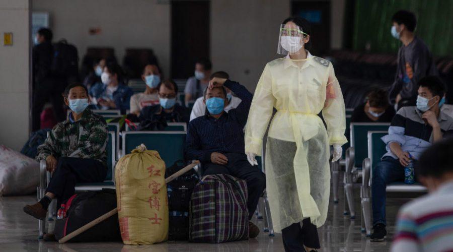 Personál dopravního podniku s obličejovým štítem prochází 30. dubna 2021 autobusovým nádražím ve Wu-chanu ve středočínské provincii Chu-pej, 2020. (STR/AFP prostřednictvím Getty Images)
