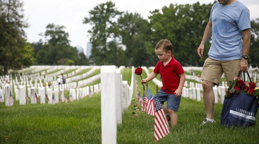Čtyřletý Matthew Murphy pokládá růži na náhrobek se svým otcem Kevinem Murphym během dobrovolnické akce na Arlingtonském národním hřbitově před Dnem uctění obětí války 26. května 2019 v Arlingtonu ve Virginii. (Tom Brenner / Getty Images)