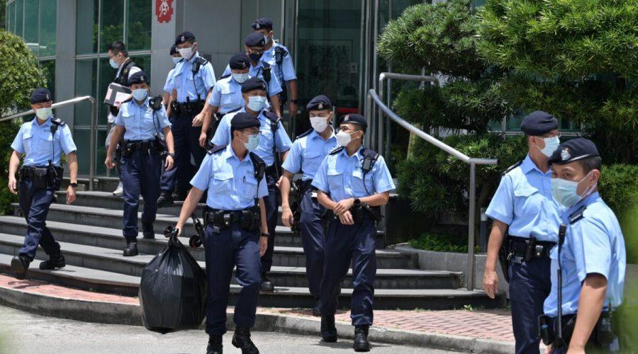 Policisté opouštějí kancelář novin Apple Daily v Hongkongu po razii více než 500 policistů, 17. června 2021. (Anthony Wallace /AFP via Getty Images)