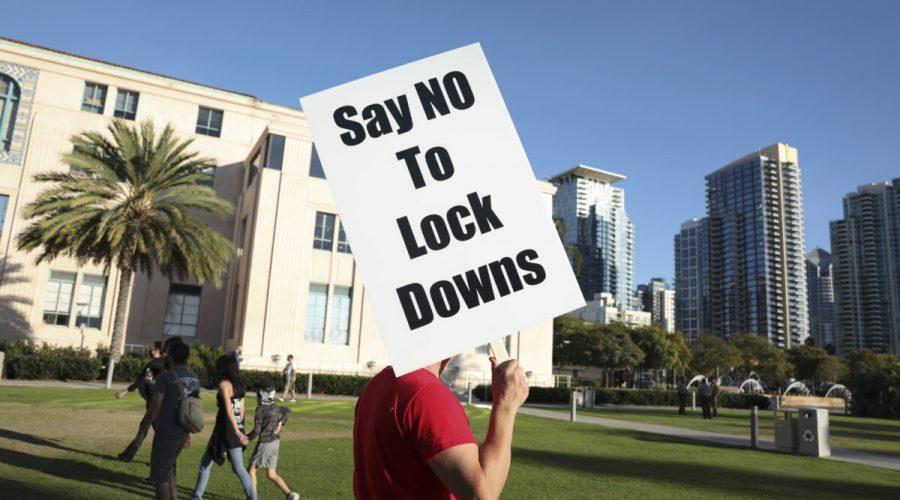 Muž drží ceduli s nápisem proti lockdonům během shromáždění u budovy okresní správy v kalifornském San Diegu, 16. listopadu 2020. (Sandy Huffaker / Getty Images)