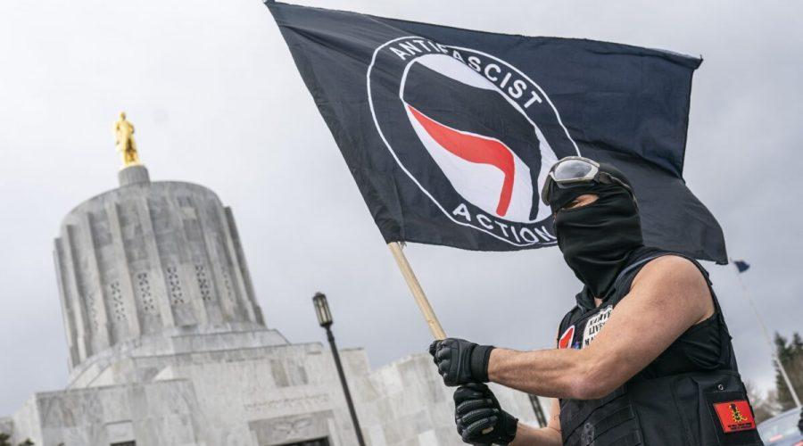 Muž mává vlajkou Antify u sídla guvernéra státu Oregon v Salemu, 28. března 2021. (Nathan Howard / Getty Images)