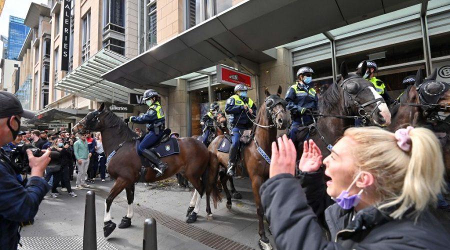Policisté na koních rozhánějí demonstranty, kteří protestují proti měsíčnímu zákazu vycházení v rámci shromáždění v australském Sydney, 24. července 2021. (Steven Saphore / AFP via Getty Images)