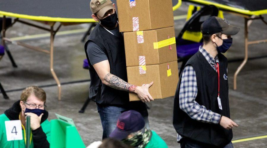 Dodavatelé pracující pro společnost Cyber Ninjas, kterou si najal arizonský Senát, zkoumají a přepočítávají hlasovací lístky z voleb 2020 v hale Veterans Memorial Coliseum ve Phoenixu v Arizoně, 1. května 2021. (Courtney Pedroza / Getty Images)
