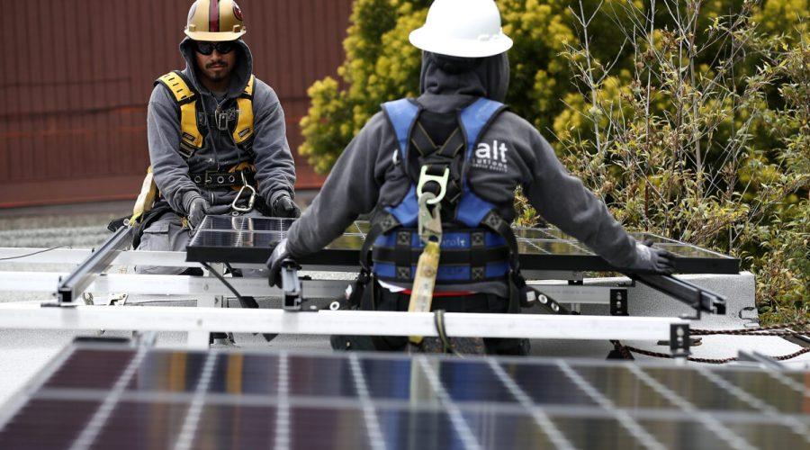 Dělníci instalují solární panely na střechu domu v kalifornském San Francisku, 9. května 2018. (Justin Sullivan / Getty Images)
