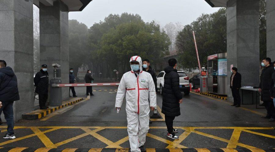 Člen ostrahy v ochranném oděvu stojí u vchodu do centra pro kontrolu a prevenci nemocí v provincii Hubei, zatímco členové týmu Světové zdravotnické organizace (WHO), který zkoumá původ covidu-19, jsou na návštěvě centra v čínském Wu-chanu 1. února 2021. (Hector Retamal / AFP via Getty Images)