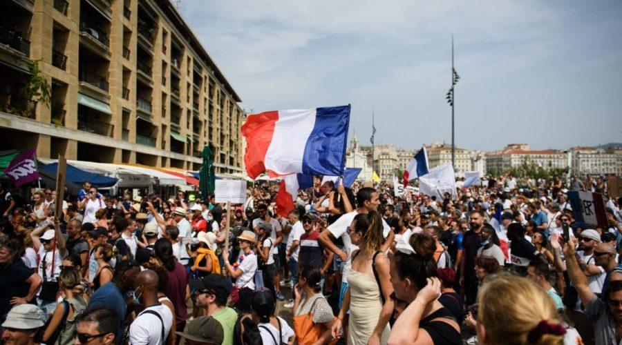 Protestující mává francouzskou státní vlajkou během demonstrace proti povinnému očkování některých pracovníků a povinnému používání zdravotního průkazu, kterou vyhlásila francouzská vláda. Marseille ve Francii, 24. července 2021. (Clement Mahoudeau / AFP via Getty Images)