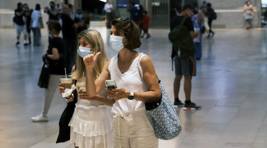 Lidé v rouškách při procházce v terminálu Grand Central v New Yorku, 27. července 2021. (Spencer Platt / Getty Images)