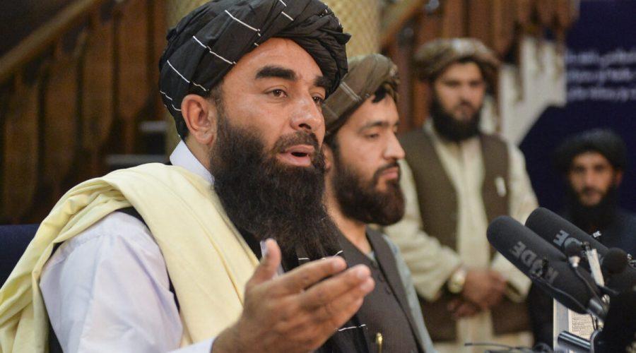 Mluvčí Tálibánu Zabihulláh Mudžáhid (v popředí) gestikuluje při projevu na první tiskové konferenci v Kábulu 17. srpna 2021 poté, co Tálibán převzal moc v Afghánistánu. (Hoshang Hashimi /AFP via Getty Images)