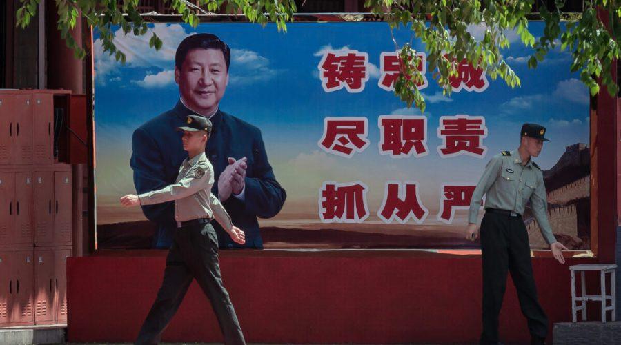 Vojáci u plakátu čínského vůdce Si Ťin-pchinga u vchodu do Zakázaného města v Pekingu 18. května 2020. (Nicolas Asfouri/AFP via Getty Images)