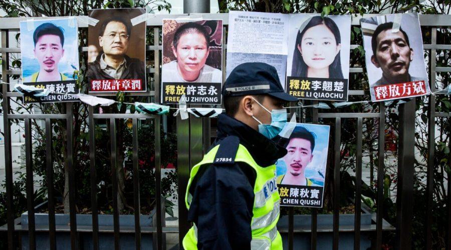 Policista prochází kolem plakátů zadržených aktivistů za lidská práva nalepených na plotě čínského styčného úřadu na protest proti zadržení prominentního protikorupčního aktivisty Sü Č'-junga Pekingem v Hongkongu v Číně, 19. února 2020. (Ilustrační foto) (Isaac Lawrence / AFP via Getty Images)