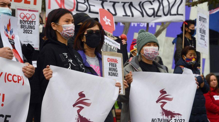 Aktivisté, mezi nimiž jsou členové místních hongkongských, tibetských a ujgurských komunit, drží 23. června 2021 v australském Melbourne transparenty a plakáty vyzývající australskou vládu k bojkotu zimních olympijských her v Pekingu v roce 2022 kvůli porušování lidských práv v Číně. (William West / AFP via Getty Images)