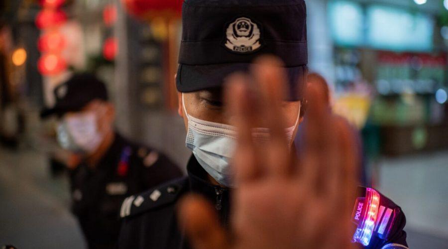 Policista s maskou na obličeji se snaží zastavit fotoreportéra, který fotografuje na ulici před komplexem nákupních center v Pekingu 13. října 2020. (Nicolas Asfouri/AFP via Getty Images)