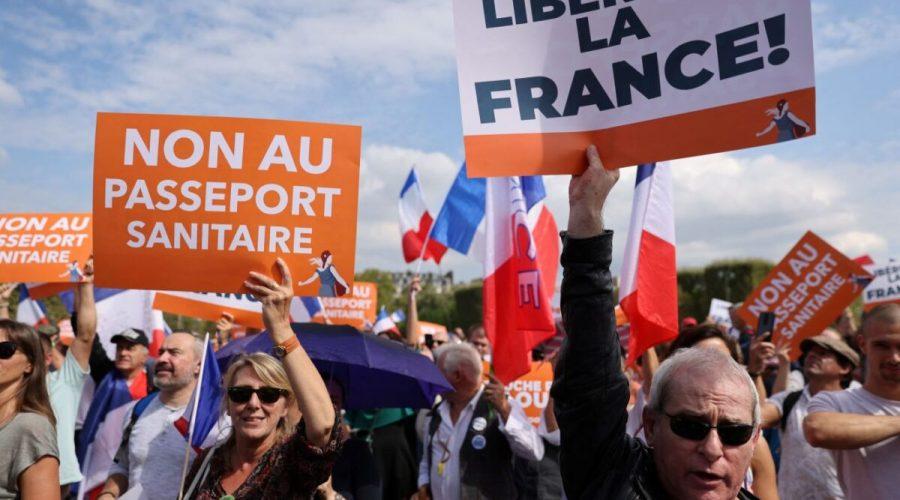 """Lidé drží transparenty s nápisy """"ne zdravotnímu pasu"""" (vlevo) a """"osvoboďme Francii"""" během demonstrace v Paříži 4. září 2021. (THOMAS COEX / AFP via Getty Images)"""