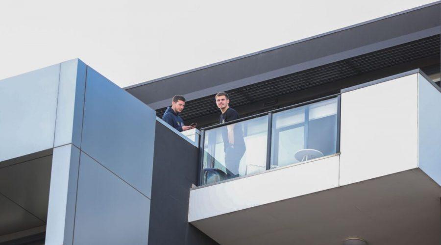 Obyvatelé bytového komplexu Ariel, kteří jsou v současné době v karanténě, jsou vidět na svém balkoně 14. července 2021 v australském Melbourne. (Asanka Ratnayake / Getty Images)