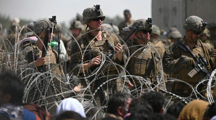 Američtí vojáci stojí na stráži za ostnatým drátem, zatímco Afghánci sedí na krajnici poblíž vojenské části letiště v Kábulu v Afghánistánu, 20. srpna 2021. (Wakil Kohsar / AFP via Getty Images)